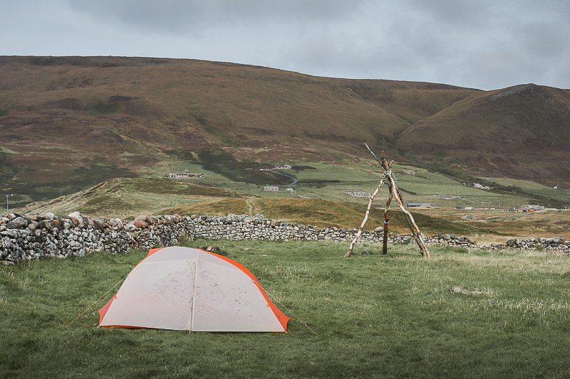 A tent in a large grassy space enclosed by an old stone wall, next to Burnmouth Bothy at Rackwick Bay on Hoy