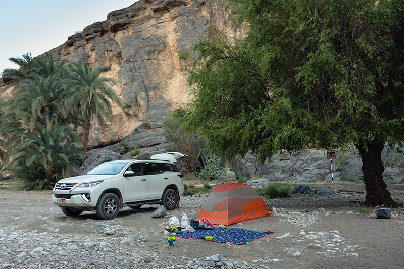 Our 4WD and tent on the sand ain Wadi Damm, Oman. Palm trees and sandy cliffs rise behind.