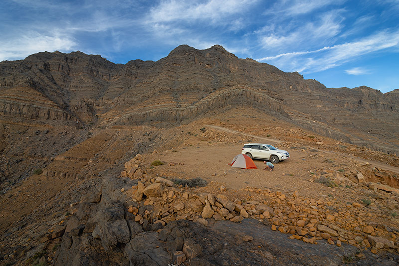 Pitching the tent in a rocky clearing among Musandam's towering mountains