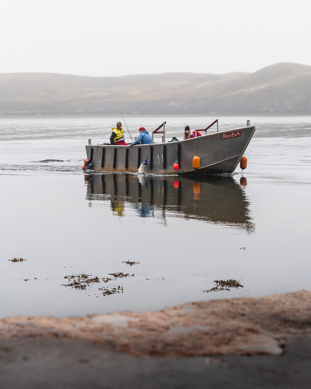 The small metal ferry boat pulling into the shore after crossing the Kyle of Durness next to the North Coast 500 route in Scotland