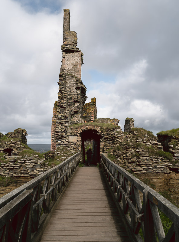 A wooden bridge leads into the ruins of Castle Girnigoe Sinclair, a top historical attraction on Scotland's North Coast 500 route.