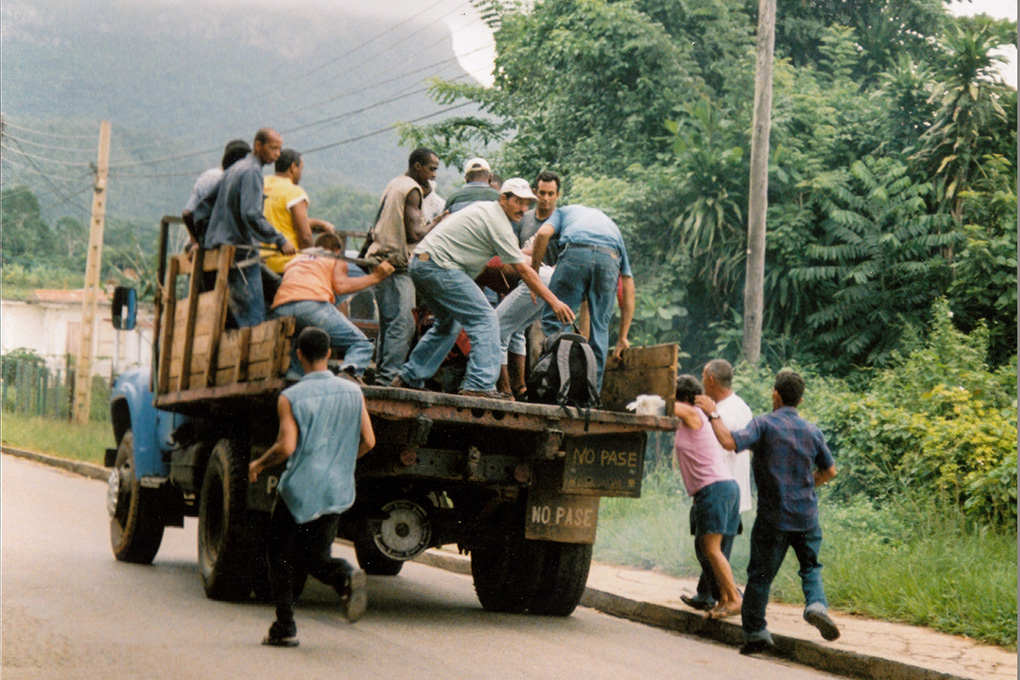 Photography Galleries - Men running to jump onto the back of a moving truck, Vinales, Cuba