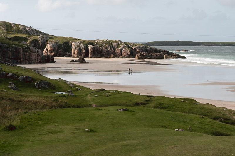 Two surfers walk across the sand in the afternoon sun at Ceannabeinne Beach, not far from Durness on the North Coast 500 route.