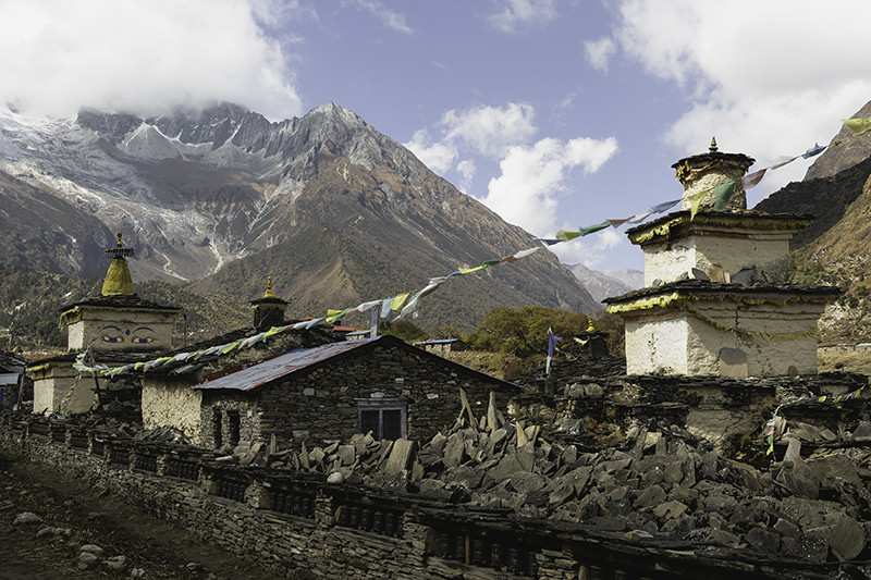 Chortens, prayer flags and stone houses against a background of mountains in Samagaun on the Manaslu Circuit