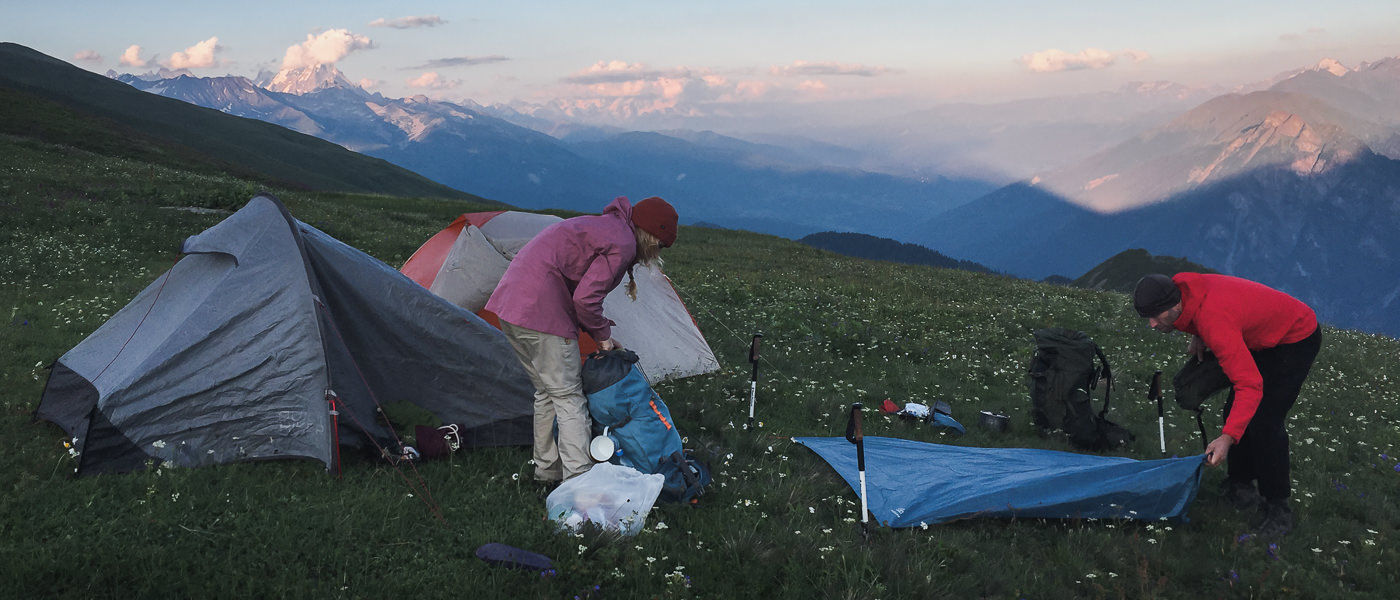Two hikers setting up camp at dusk, below Utviri pass on the Chuberi to Mestia section of the Transcaucasian Trail in Svaneti, Georgia