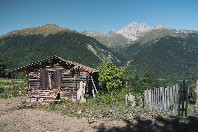 A wooden hut in the village of Latsumba with mountains as a backdrop, on the Chuberi to Mestia section of the Transcaucasian Trail in Svaneti, Georgia