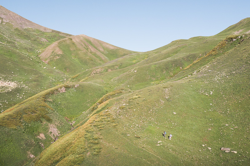 Two hikers climb the green slopes towards Utviri pass on the first day of the Chuberi to Mestia section of the Transcaucasian Trail in Svaneti, Georgia