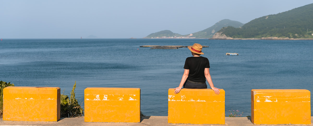 A person sits on a yellow painted concrete block enjoying the warm afternoon colours at the coast on Chuja-do, near the end of Olle Trail Route 18-1