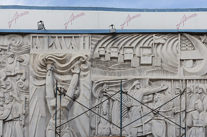 The prominent 'October' relief at the Arman Cinema, partly hidden behind scaffolding with some restoration work underway. Armed soldiers advance on horseback, a flame wielding female represents the Motherland and a convoy of flag bearing tractors plough fertile lands. It's quite something.