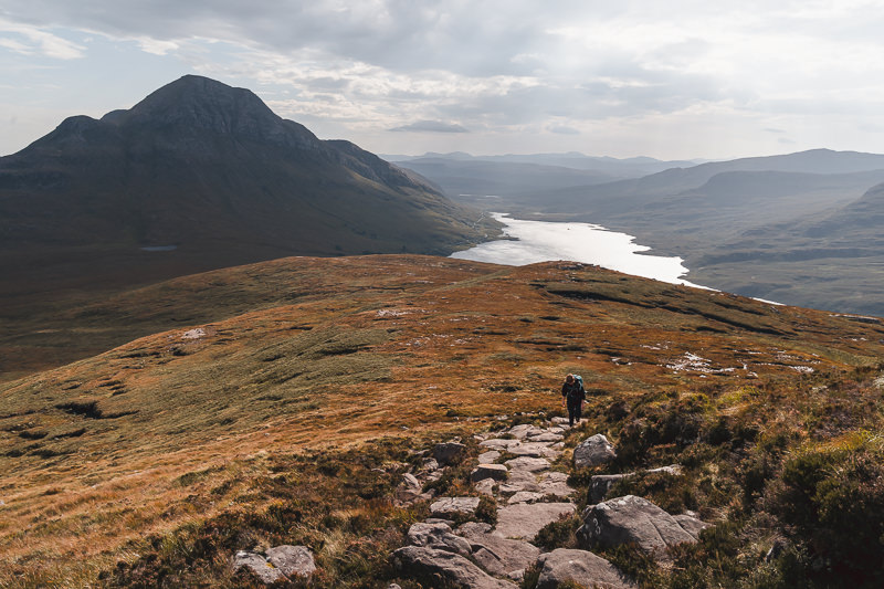 A lone hiker climbing the eastern side of Stac Pollaidh while the surrounding landscape lies in contrasting light and shadow