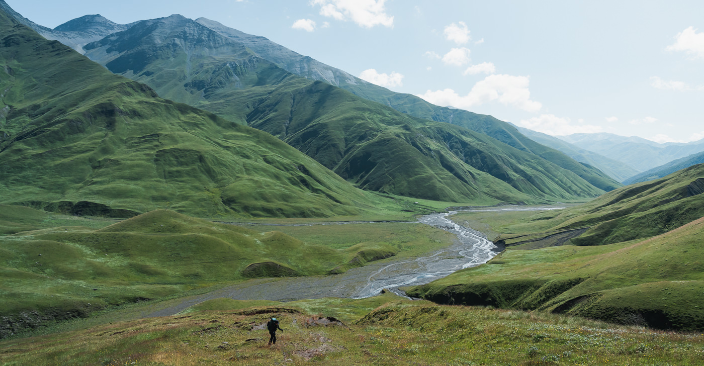 A hiker leaving the now wide Tushetis Alazani river valley behind while climbing a switchback trail towards Sakorno Pass on Day 3 of the Tusheti to Pankisi Valley trek in Georgia