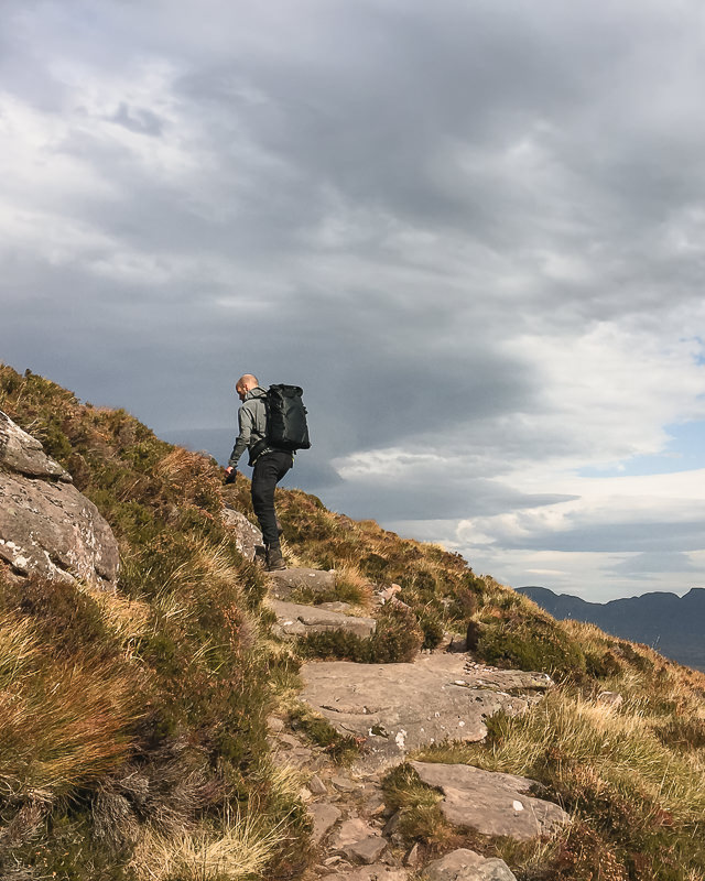 A hiker wearing the Wandrd Prvke 31 climbing the trail up Stac Pollaidh on an overcast day in the Scottish Highlands