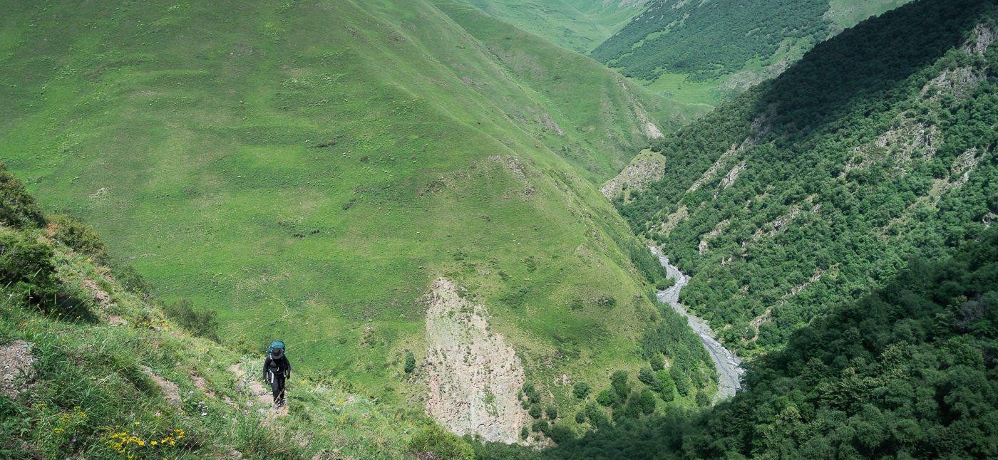 The river and valley floor falls away as a hker climbs the steep trail up to Khidotani Ridge on the Shatili Omalo trek in Georgia