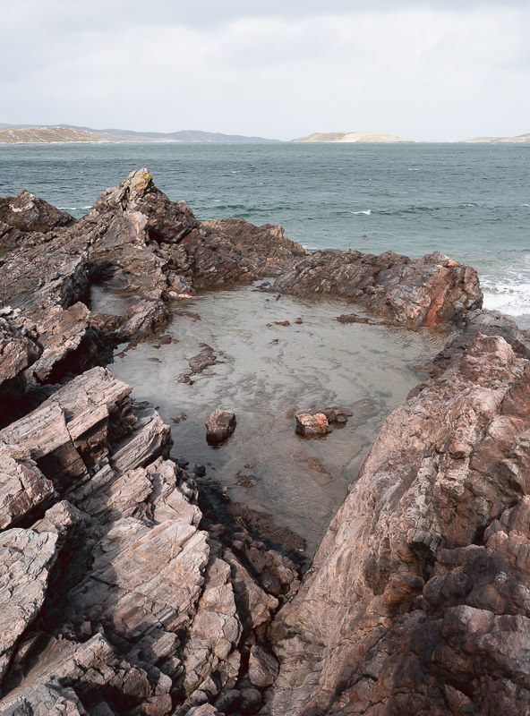 A diamond shaped rockpool, framed by jagged shards, on the shore at Coldbackie Beach.
