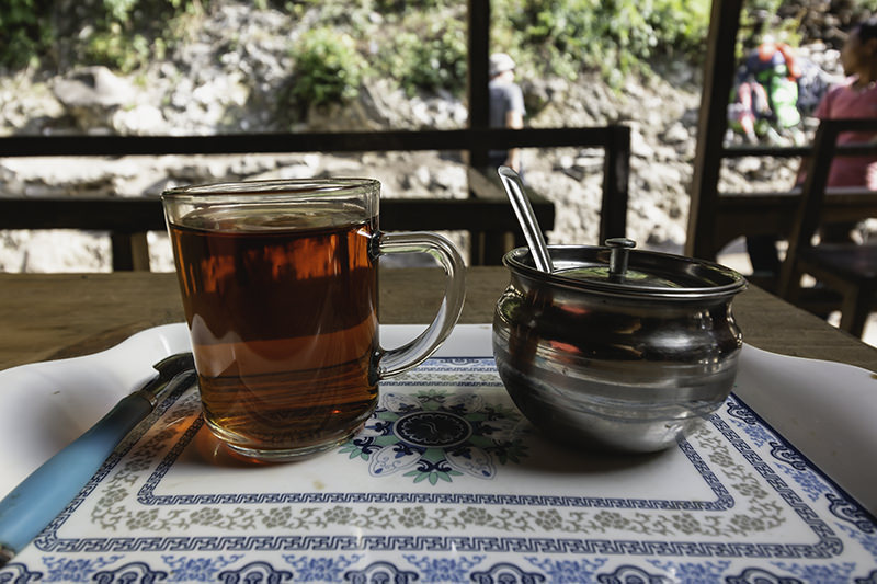 A cup of tea and metal bowl of sugar on a table at a rest stop on the Manaslu Circuit Trek