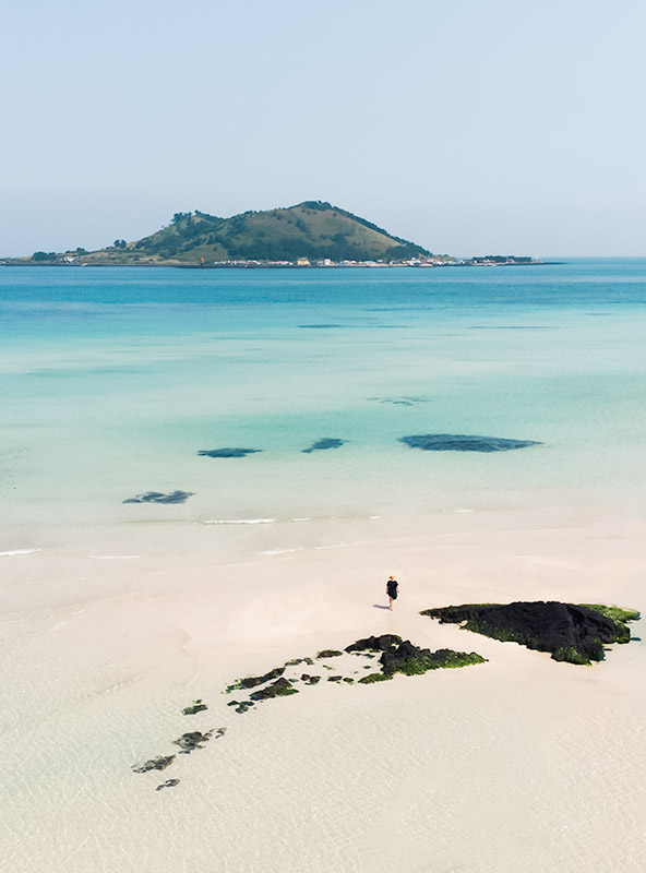 An aeriel view of pristine white sand, turquoise blue water, black vocanic rocks, a lone figure and Biyangdo Island in the distance. This is Geumneung Beach, one of the absolute best beaches on Jeju Island.