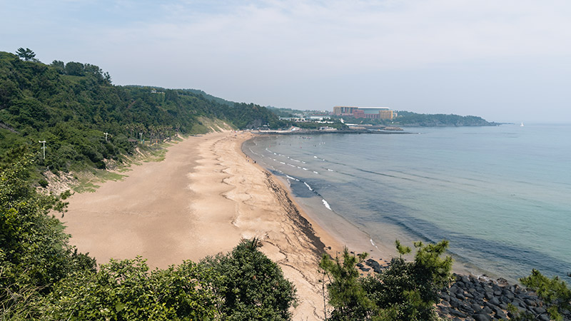 The golden sand of Jungmun Beach, one of the best beaches on Jeju, seen from the west.