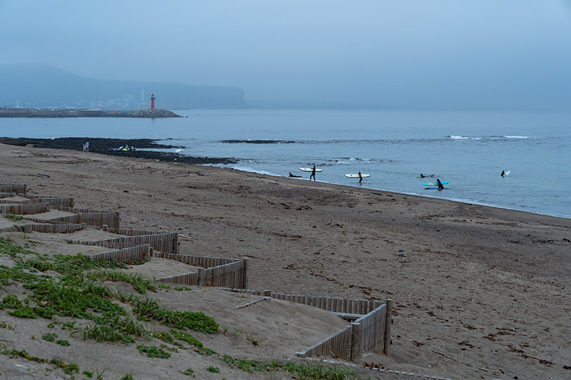 Surfers make their way out of the sea in blue hour at Sagye Beach, one of the best beaches on Jeju.
