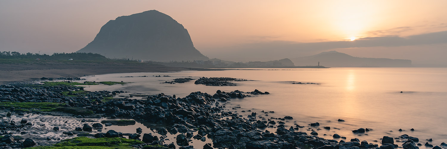 Sunrise over Sanbangsan and Sagye Beach, one of the best beaches on Jeju to watch sunrise.