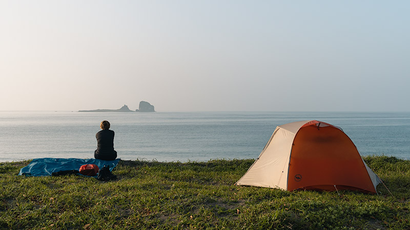 A person sits on the grass next to a tent behind Sagye Beach, looking out to sea in the bright morning light.