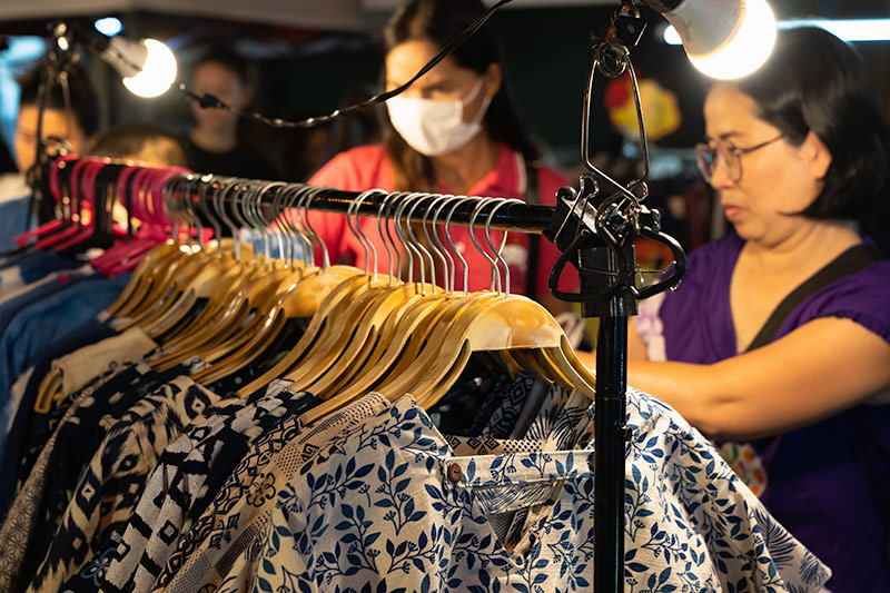 Women peruse the traditional Lanna clothing on racks at the San Kamphaeng Saturday Market in Chiang Mai, Thailand