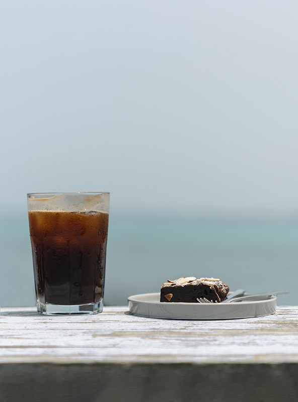A condensation covered glass of iced coffee and a brownie, sat on a table made from old driftwood at Geumneung Beach on Jeju Island