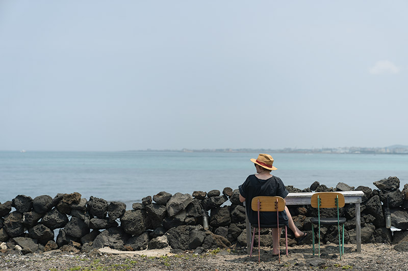 A person sits at a table in front of a dry stone black volcanic rock wall looking at the blue sea at Geumneung Beach, one of the best beaches on Jeju.