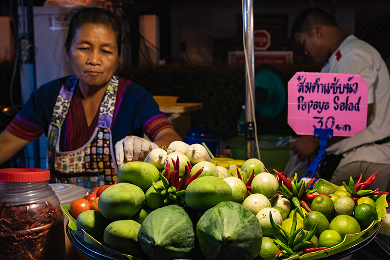 A lady prepares somtum (spicy papaya salad), choosing her fruit from a big bowl of green topped with red chillies at the San Kamphaeng Saturday Market in Chiang Mai, Thailand