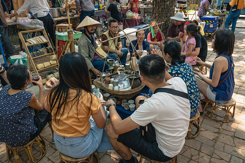 People sit on low stools being served artisan coffee from a gentelman in traditional dress at the Jingjai Rustic Market in Chiang Mai, Thailand
