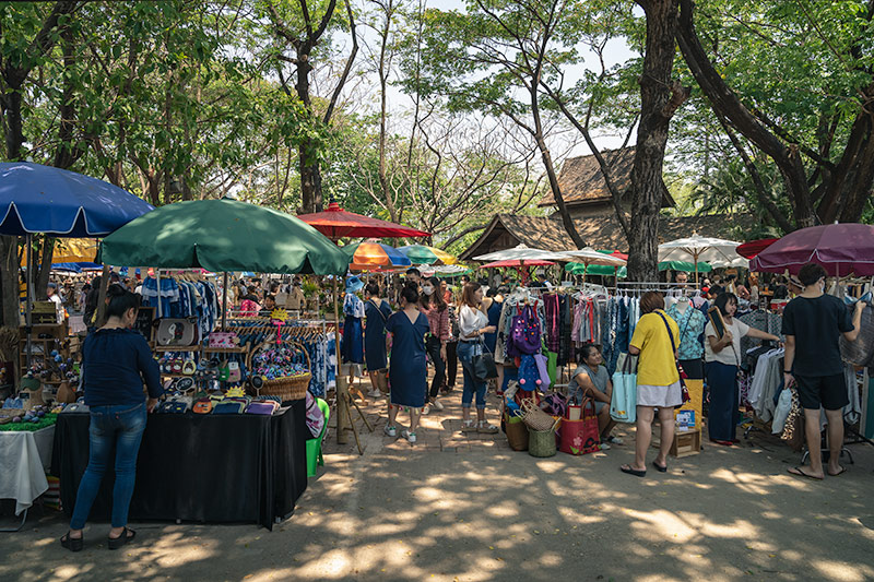 The crowds browse the Sunday market stalls for clothes and handicrafts beneath sun dappled trees at the Jingjai Rustic Market in Chiang Mai, Thailand