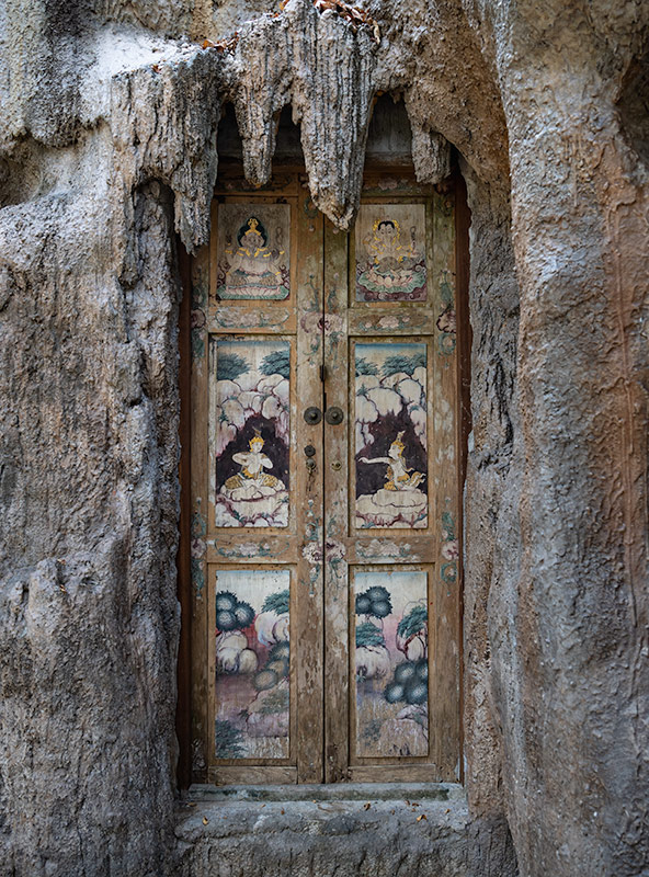 Old door and twisted rock formation at Wat Pha Lat on Doi Suthep mountain in Chiang Mai, Thailand