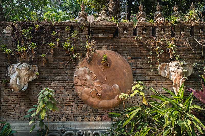 Orange brick walls, elephant sculptures and green vegetation at Wat Pha Lat in Chaing Mai, Thailand