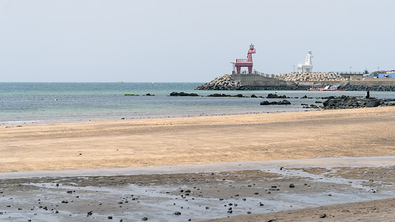 Iho Taewoo Beach near Jeju City, the two distinctive horse shaped lighthouses in the background.