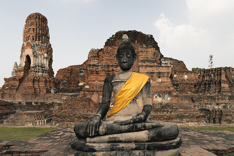 A buddha with a yellow sash sits crosslegged in front of ruins at Wat Mahatat in Ayutthaya
