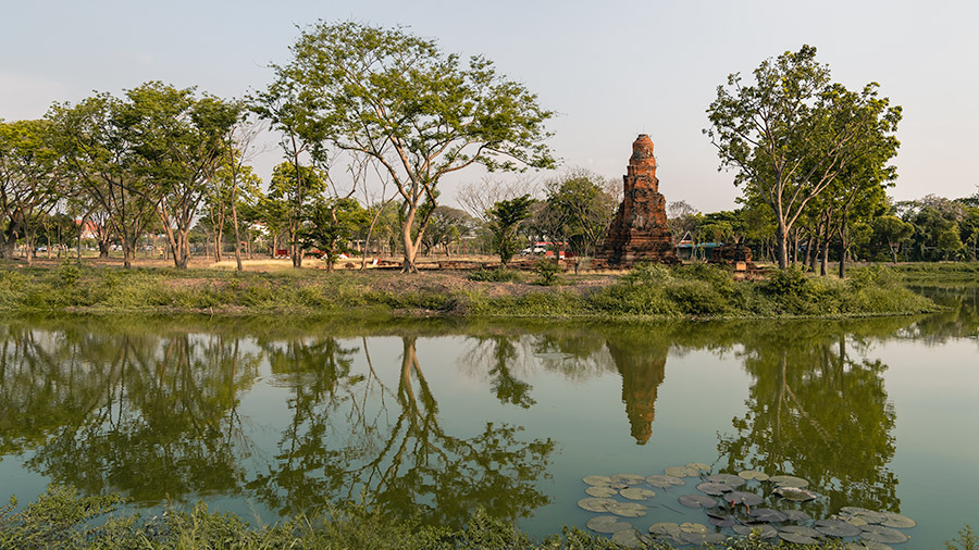 Trees and and small ruined buldings are reflected in the river in the Ayutthaya Historical Park, Thailand.