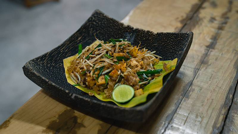 A bowl of Pad Thai sitting on a bench in Burinda, Ayutthaya, Thailand.