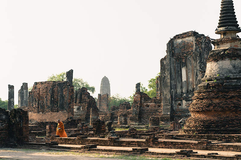 A monk walks through the towering ruins of Wat Phra Si Sanphet after sunrise at Wat Phra Si Sanphet in Ayutthaya, Thailand