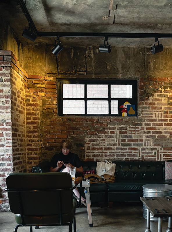 Person sitting on a leather couch in Sooda Coffee Roasters in Tongyeong