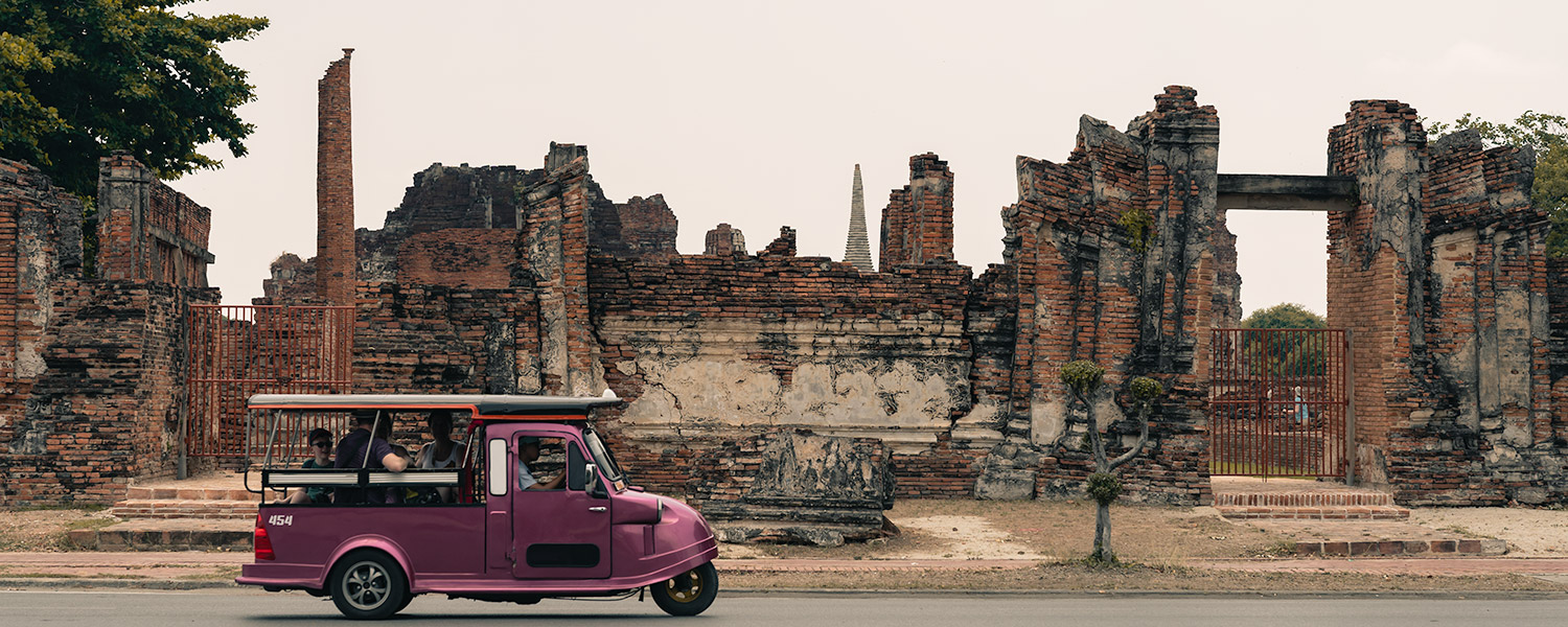 A magenta tuk tuk carries passengers on the road past the ruined walls in front of Wat Mahatat in Ayutthaya, Thailand