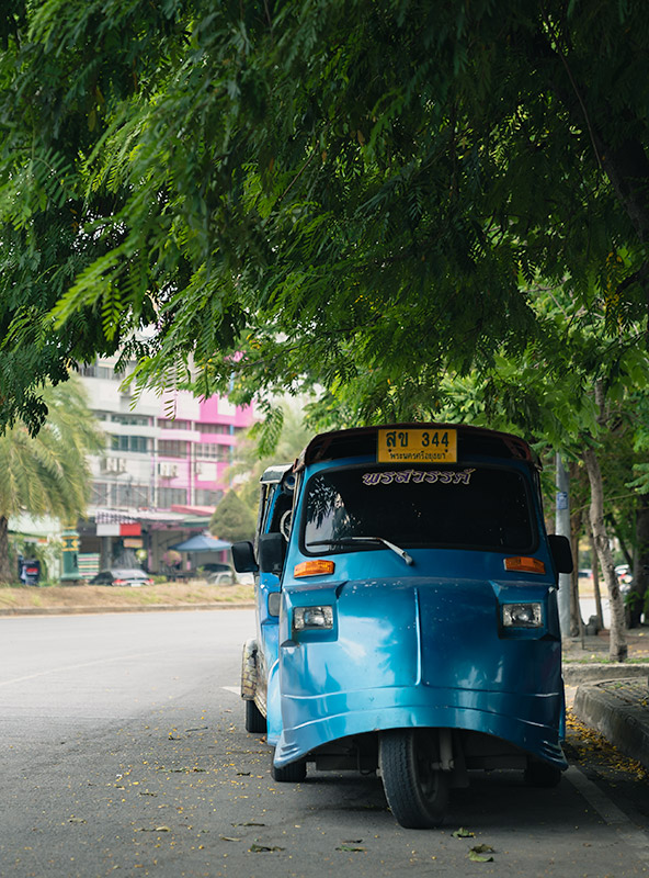 A bright blue tuk tuk parked below a leafy green tree on the streets of Ayutthaya, Thailand.