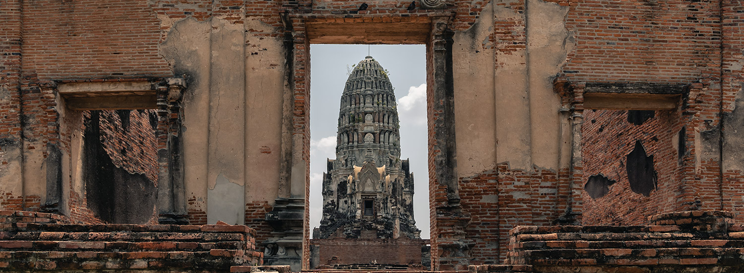 The central prang fo Wat Ratchaburana framed through the ruined front gate in Ayutthaya, Thailand