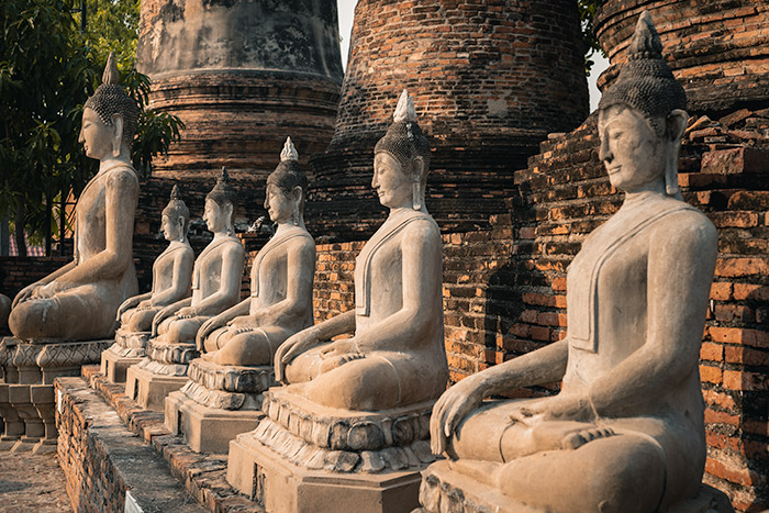 A row of sunlit stone Buddhas at Wat Chai Mongkhon in Ayutthaya, Thailand
