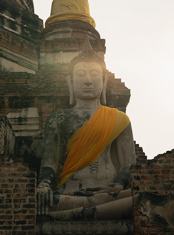 A huge buddha statue with a yellow sash caught in the late afternoon sun at Wat Yai Chai Mongkhon in Ayutthaya, Thailand