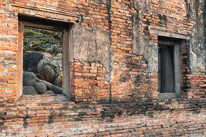 The head of a reclining Buddha through the window of a crumbling wall in Ayutthaya, Thailand.
