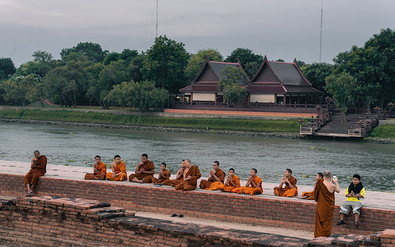 A row of monks sit crosslegged on the wall in front of the river at dusk in Ayutthaya, Thailand