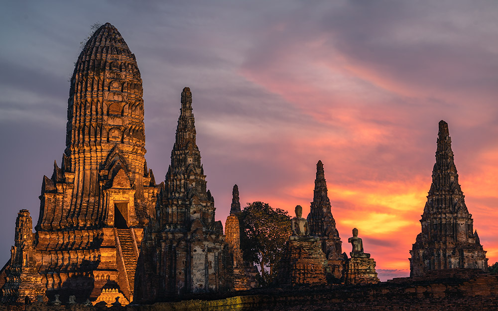 The sunset is bright orange,yellow and pink in the sky above the magnificent buildings of Wat Chaiwatthanaram in Ayutthaya