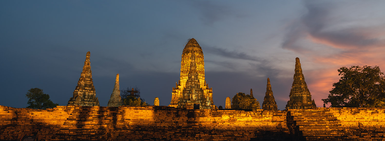 The floodlit prangs of Wat Chaiwatthanaram at dusk in Ayutthaya, Thailand