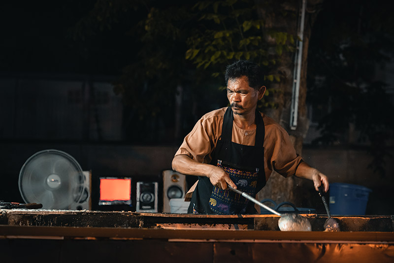 A man showing skill and enthusiasm while cooking oyster omelete in a huge pan outdoors at the Ban Lan Night Market in Ayutthaya, Thailand.
