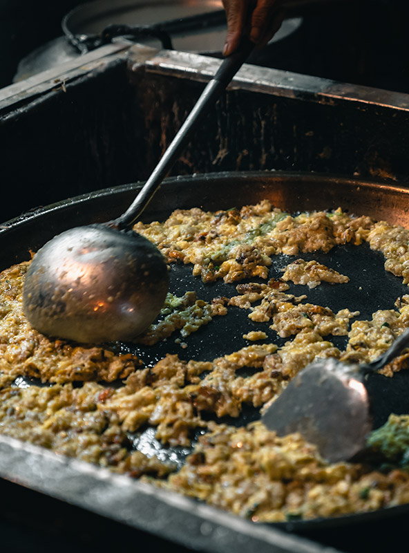 A close up of oyster omelete being cooked in a large flat metal pan at the Ban Lan Night Market in Ayutthaya, Thailand.