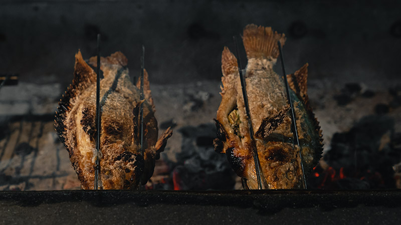 Two whole fish are turning on a spit over red hot charcoal a the Ban Lan Night Market in Ayutthaya, Thailand